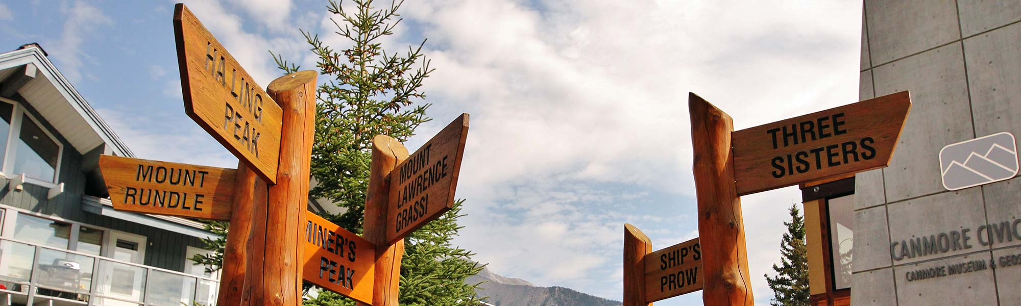 Outside the Canmore Civic Center, signs pointing to different points of interest.